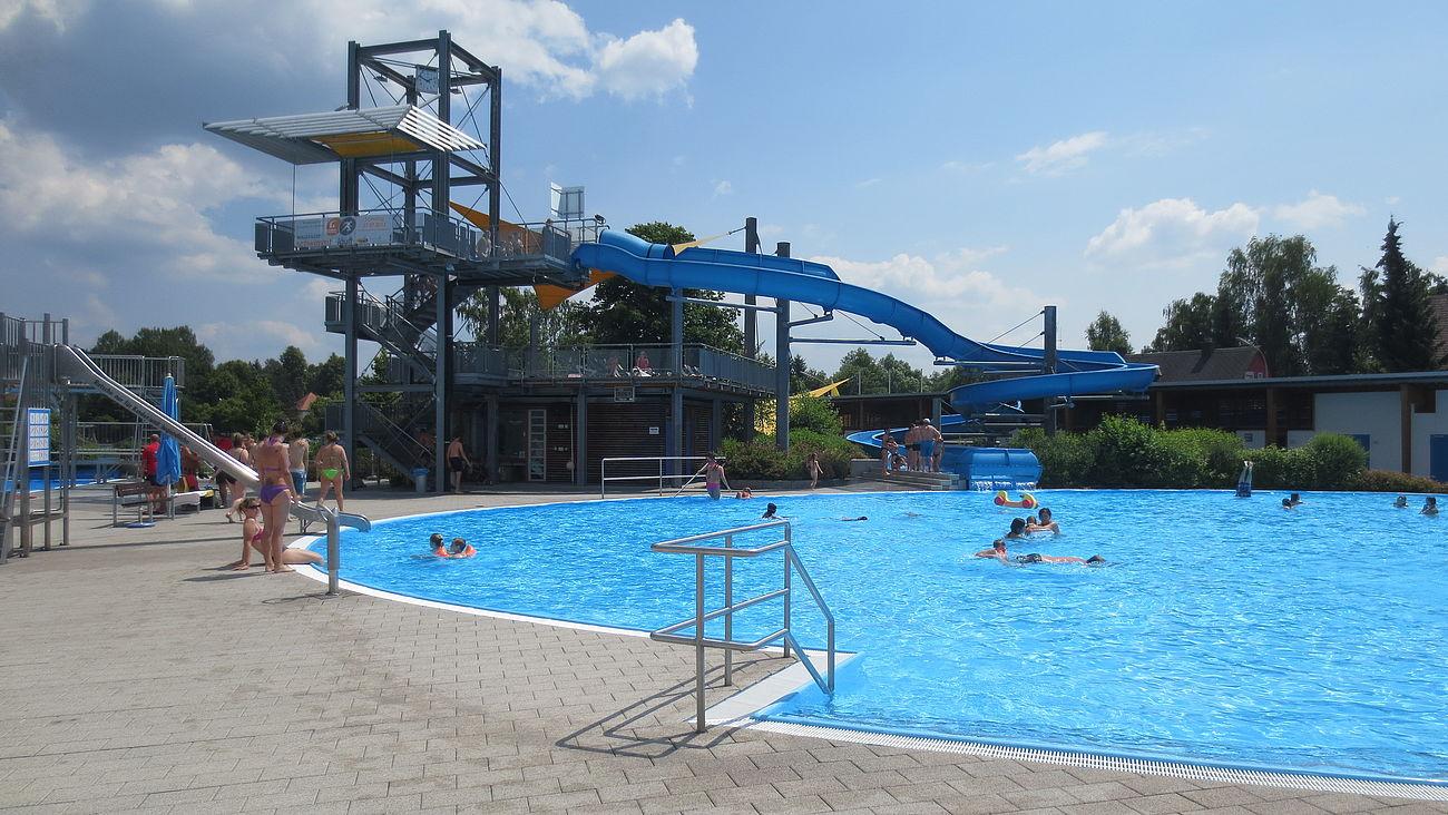 Blick auf das Nichtschwimmerbecken im Egrensisbad mit Wasserrutsche im Hintergrund.